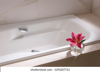 Relaxing at Home Luxury Bathroom Interior White Empty Bathtub Pink Lily Flower in small Glass Vase Nobody Cleanliness Elegance Room Decor Marble Texture