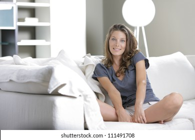 Relaxing at home. Portrait of a young woman smiling on white couch