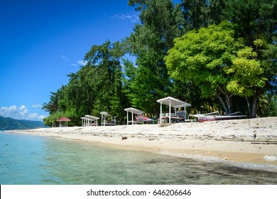 Relaxing houses with green trees on beach at Gili Islands in Lombok, Indonesia. Lombok is known for beaches and surfing spots, particularly at Kuta and Banko Banko.