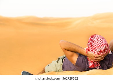 Relaxing male tourist lying on top of a desert hill with his hands behind head.