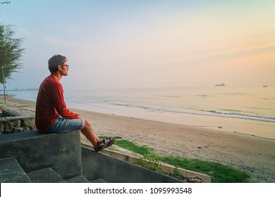 relaxing man at nature/ Young indian man sitting and looking at sunset sea beach
