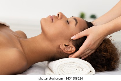 Relaxing Massage. Afro Woman Receiving Head Massage At Spa Salon, Side View