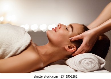 Relaxing massage. Woman receiving head massage at spa salon, side view