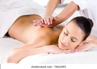 Relaxing massage for young beautiful woman in the spa salon - horizontal