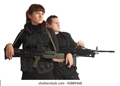 Relaxing military woman with the machine gun. Military man on the background. Focus point on the woman.