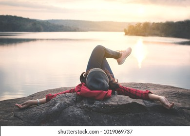 Relaxing moment Asian tourist sleeping on rock waiting for sunset ,enjoying time on holiday concept ,color of vintage tone