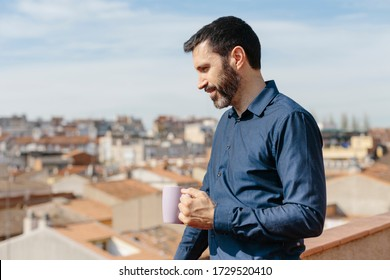 Relaxing moment of a middle-aged man standing on the balcony drinking coffee