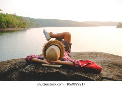 Relaxing moments, Asian young boy relaxing outdoor on the lake in sunset. Relax time on holiday concept travel. Hipster tone style.