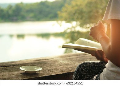 Relaxing moments , Cup of coffee and a book on wooden table in nature background, color of vintage tone and soft focus.
