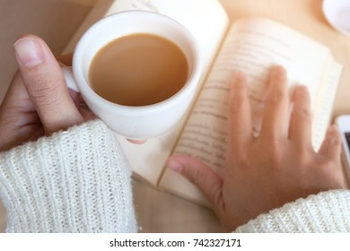 Relaxing moments, Cup of coffee and a book on wooden table in nature background, color of vintage tone and soft focus, winter morning concept.