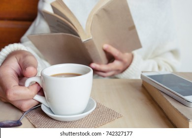 Relaxing moments , Cup of coffee and a book on wooden table in nature background, color of vintage tone and soft focus, winter morning concept.