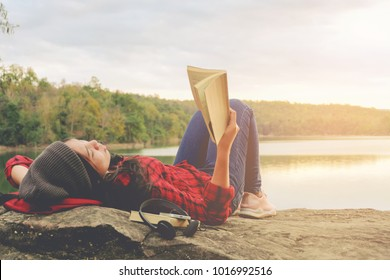 Relaxing moments, Young woman reading a book by the lake. Solo relaxation, color of Hipster Tone.