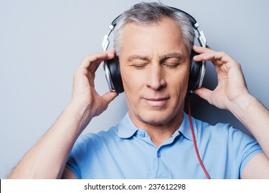 Relaxing music time. Portrait of senior man in headphones listening to music keeping eyes closed while standing against grey background