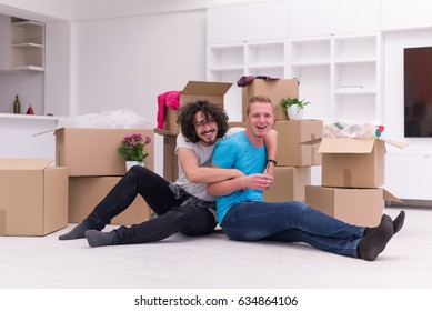 Relaxing in new house. Cheerful young gay couple sitting on the floor while cardboard boxes laying all around them