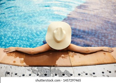 Relaxing on Beach Resort. Beautiful Back Side of Sexy Woman in big Hat Enjoying Summer from Swimming Pool. Luxury Traveling and Tourism Concept