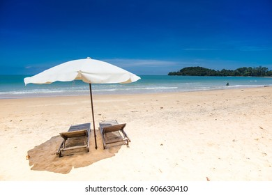 relaxing on the beach on vacation holiday and weekend on the white sand clean and clear beach with wooden chair and umbrella resort and spa for traveling with blue sky with family