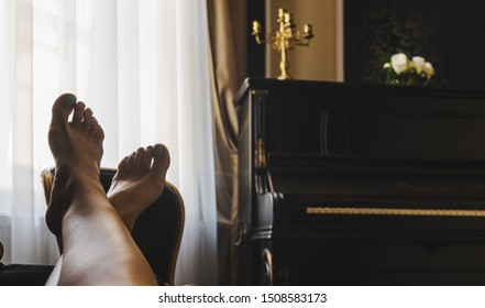 Relaxing on the couch with piano in the background, close-up on woman bare feet up