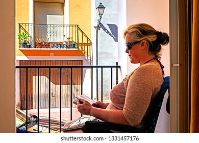 Relaxing on holiday or vacation - attractive woman reading and chilling out in the sunshine.