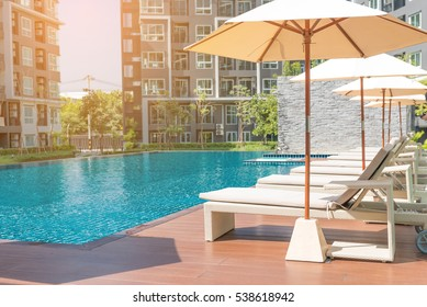 Relaxing rattan chairs with pillows beside swimming pool