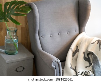 Relaxing reading corner with big grey armchair, cozy plaid, wooden board and exotic green plant.