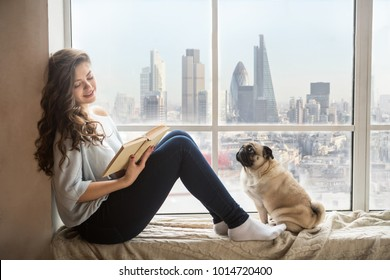 Relaxing reading woman with London city on backgraund. Amazing window view