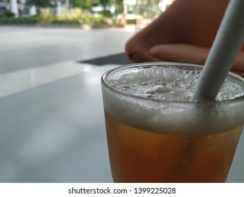 Relaxing with a refeshing and chilling Peach icetea on sofa .