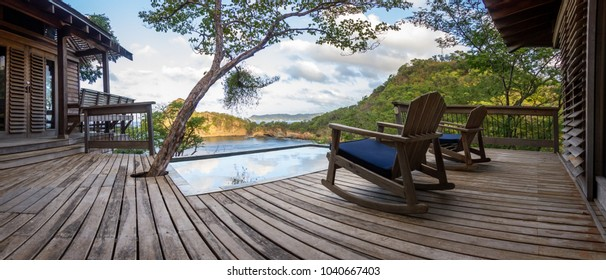 relaxing scene with a calm pool and a wooden deck and building with the pacific ocean in the background