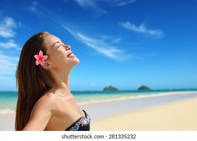 Relaxing serene woman portrait on Hawaii Lanikai beach. Young mixed race female by water relaxed during summer travel holidays on Oahu, Hawaii, USA with Mokulua Islands.