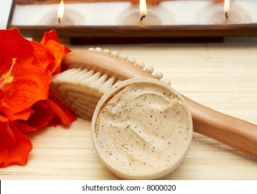 Relaxing spa scene with nourishing and exfoliating body scrub, brush massager on light wooden background and candles