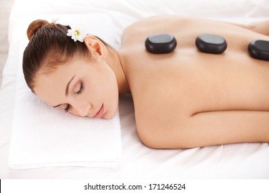 Relaxing at spa. Top view of attractive young woman lying on front and keeping eyes closed with spa stones on her back