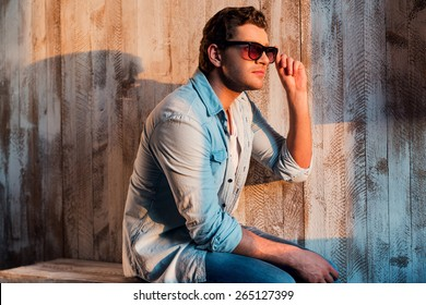 Relaxing in sun rays. Handsome young man looking away and adjusting his sunglasses while sitting against the wall