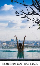 Relaxing at swimming pool on rooftop, Woman enjoying the view with arms raised from swimming pool