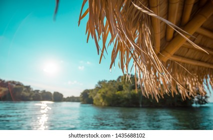 relaxing tiki hut on a lake on a sunny cloudy day at dusk