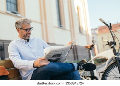 relaxing time in city. man reading newspaper in city , bicycle in blurred background
