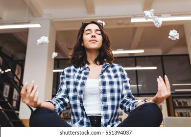 Relaxing time joyful young brunette woman having meditation on table in office surround flying papers. Taking a break, pause, smart student, relaxation, great success, dreaming