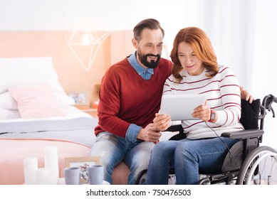 Relaxing together. Happy loving bearded man and disabled woman of middle age smiling and using a tablet while sitting