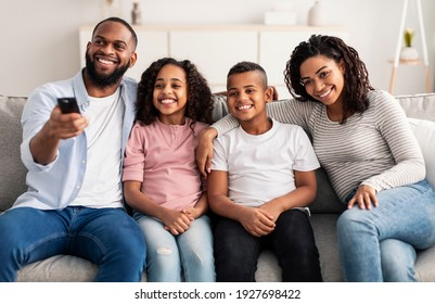 Relaxing Together. Portrait of happy young African American family watching television, parents sitting with their two children on comfortable sofa in the living room, laughing at the program