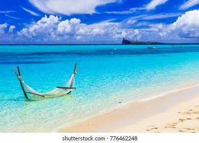 Relaxing tropical holidays with hammock in the turquoise sea.