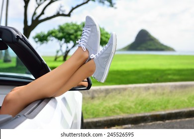 Relaxing vacation car road trip travel with feet up the window. Convertible car holiday concept with female legs in front of Oahu landmark : Chinaman's Hat in Hawaii, USA.