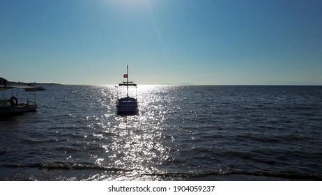a relaxing view of the sea and sun from the beach. Sunset. sunrise. fishing boat in the sea. Turkish bayraklı balıkçı teknesi.  - Shutterstock ID 1904059237
