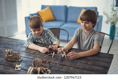 Relaxing while playing. Creative curious boys sitting at the table and playing while having wooden constructors in their hands