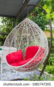 Relaxing white Vintage hanging chair with red seat in garden.