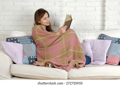 Relaxing woman lying comfortable in sofa with book