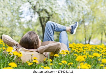 Relaxing woman lying on spring blooming meadow. Girl resting in summer park. Enjoy life, having fun, leisure, relaxation, springtime, lifestyle concept
