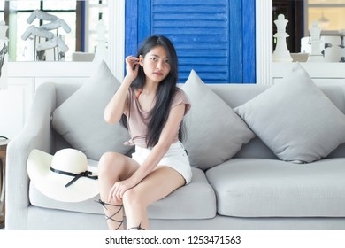 Relaxing woman sitting comfortable in sofa lounge chair smiling happily