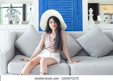 Relaxing woman sitting comfortable in sofa lounge chair smiling happy looking at camera