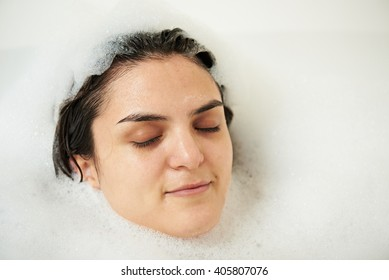 relaxing young girl in bathroom around soap bubbles