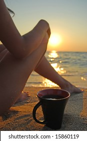 Relaxing young woman on a beach with a cup of coffee