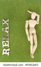 relax:wood model relax with paper cut alphabet on green grass