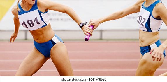 relay race passing of baton women relay team in athletics
